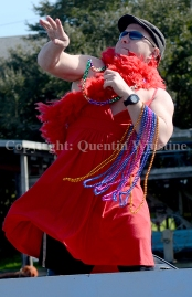 "A Krewe of Bilge member on a boat float titled ""Red Dress Run"" tosses beads to the crowd along the Eden Isles canal in Slidell on Saturday, February 15, 2014."
