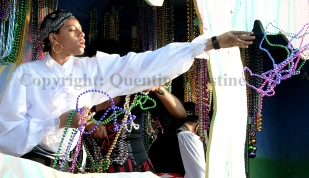 A member of Claude tosses a beads to the crowd during the parade on Sunday, February 9, 2014.